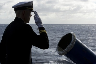 Lt. David L. Duprey salutes after committing the cremated remains of a former Sailor to the deep during a burial-at-sea ceremony