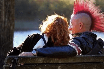 Alexis Kidd sitting on a park bench with a guy with a mohawk