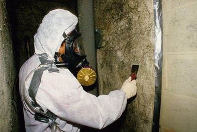 worker in full respirator gear checking in home asbestos