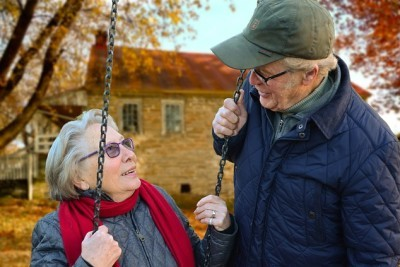 Woman on a swing and a man talking to her