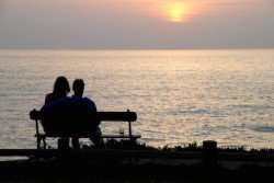 couple sitting on a bench watching the sunset in August, 2010