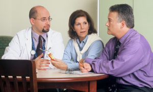 Image of doctor talking to patient and caregiver.