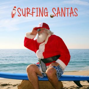 Image of a Santa sitting on a surfboard on the beach looking out at the ocean. Image reads: Surfing Santas