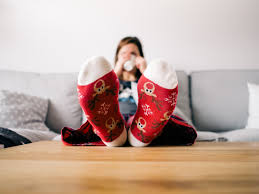 Person wearing Christmas socks, sitting on a couch and drinking out of a cup.