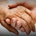 Image of caring hands. An elderly hand holding a younger hand.
